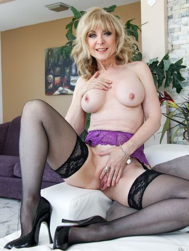 Busty Milf Porn Star Nina Hartley Rides A Hot Young Dude In Her Black Stockings.